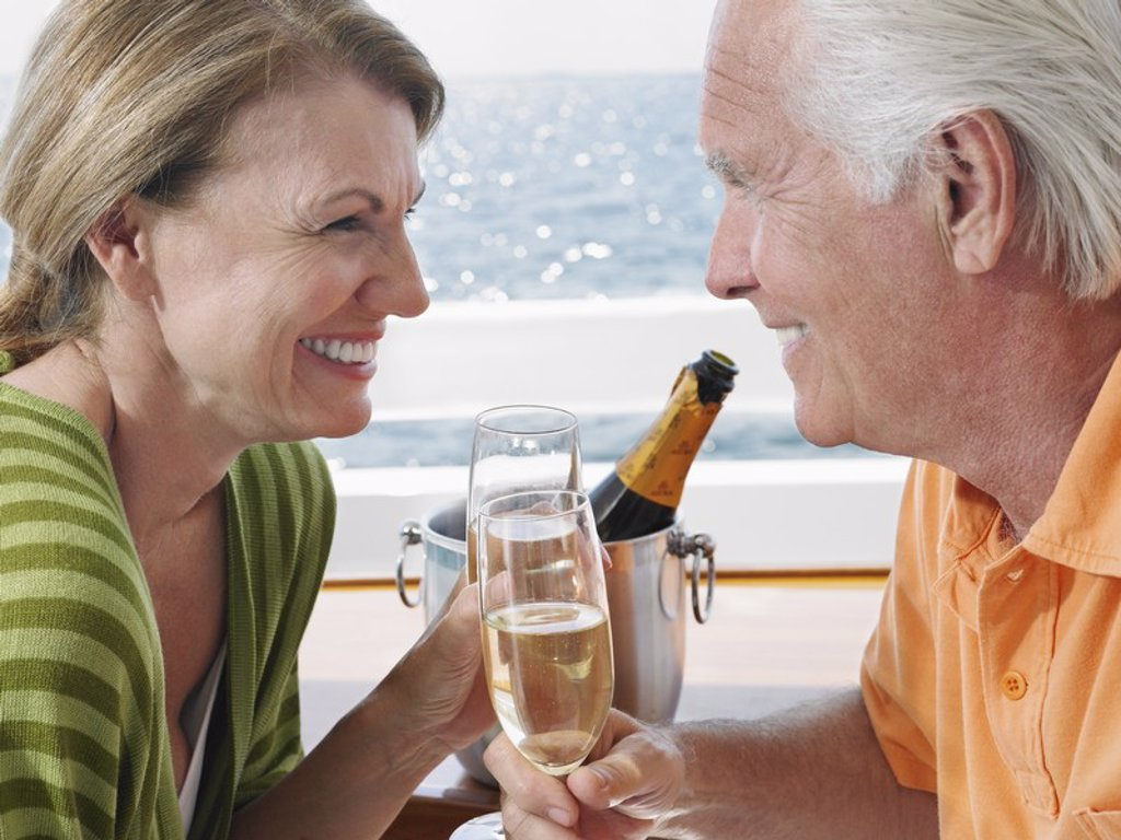 Middle_aged couple drinking champagne on yacht side view close_up : Stock Photo