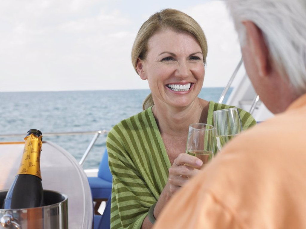 Middle_aged couple drinking champagne on yacht : Stock Photo