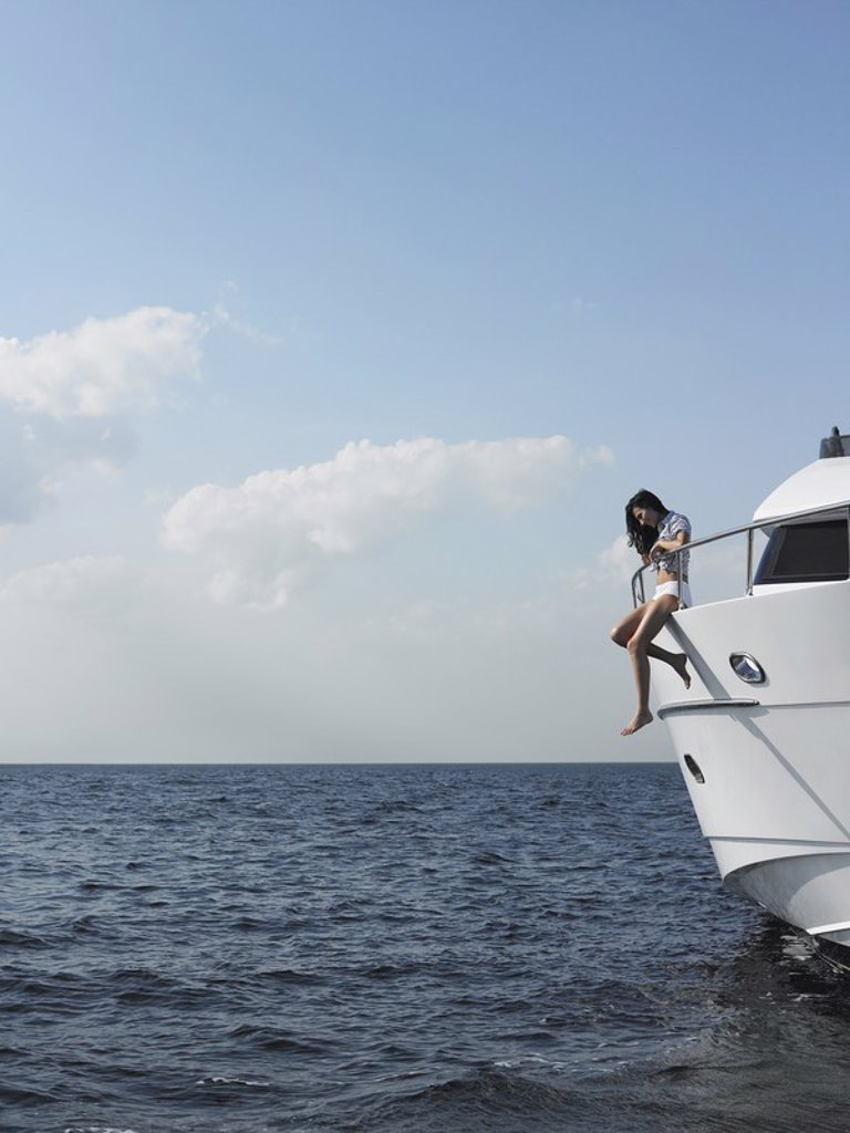Stock Photo: 1654R-17882 Young woman sitting at edge of yacht with legs dangling overboard side view