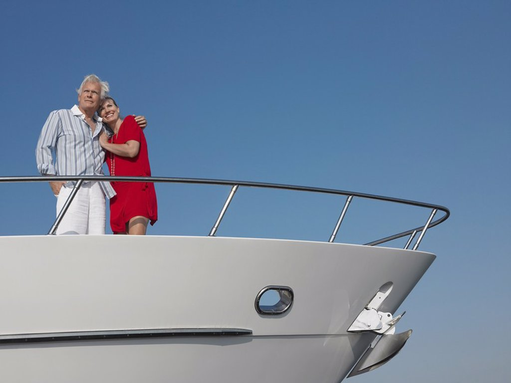 Middle_aged couple standing in bow of yacht : Stock Photo