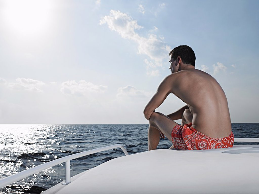 Young man sitting at edge of yacht looking at sea back view : Stock Photo