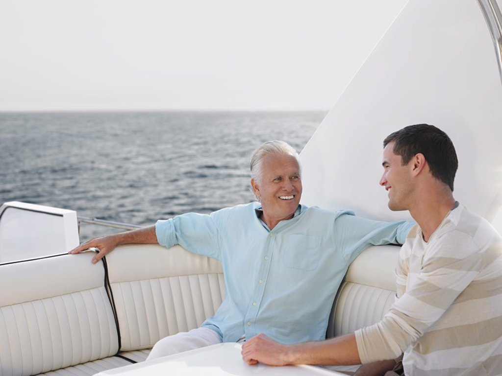 Young and middle_aged man talking on yacht : Stock Photo