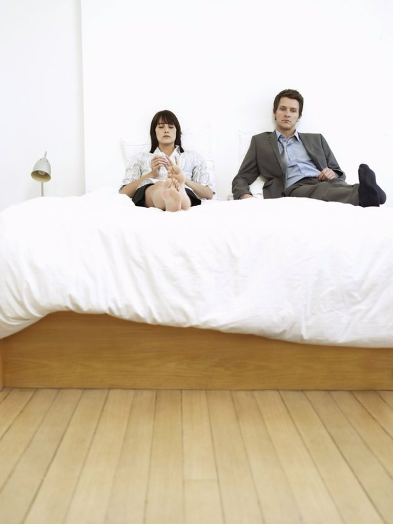 Young business couple sitting on bed : Stock Photo