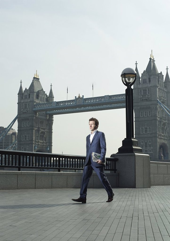 Stock Photo: 1654R-17979 Young business man walking in front of Tower Bridge