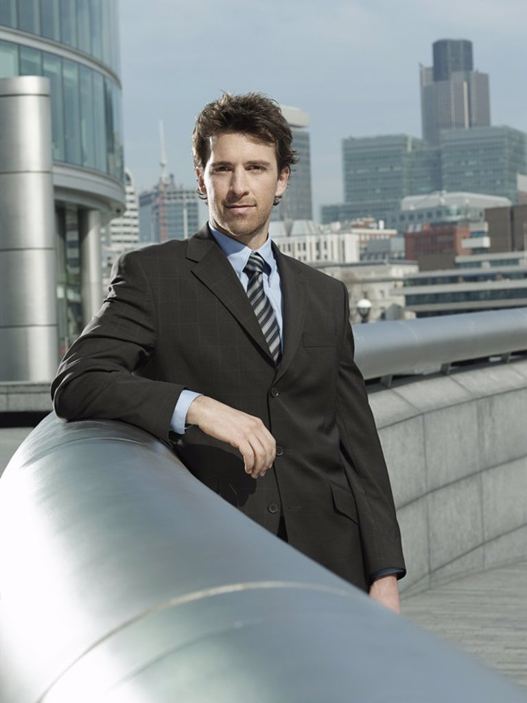 Young businessman leaning on pipe outside building : Stock Photo