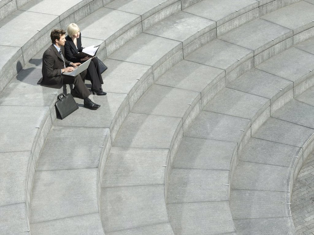 Business man and woman sitting on spiral stairs using laptop elevated view : Stock Photo