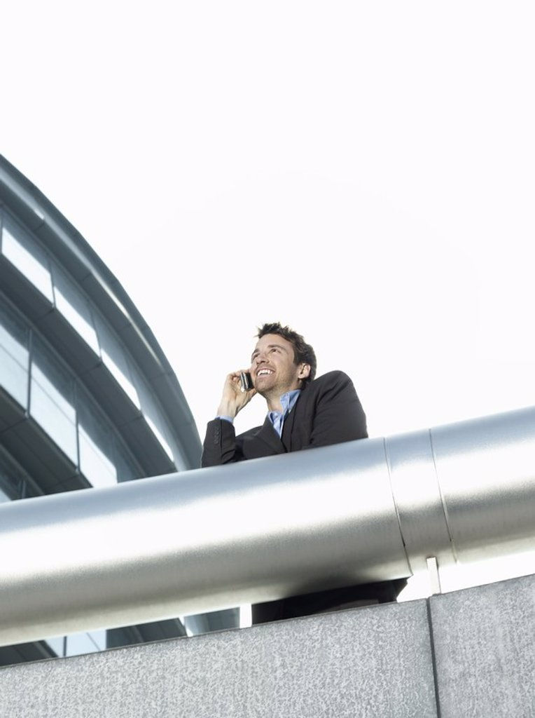 Businessman standing behind pipe outside office building using mobile phone low angle view : Stock Photo