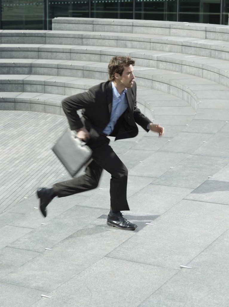Businessman with briefcase running up steps outdoors side view : Stock Photo