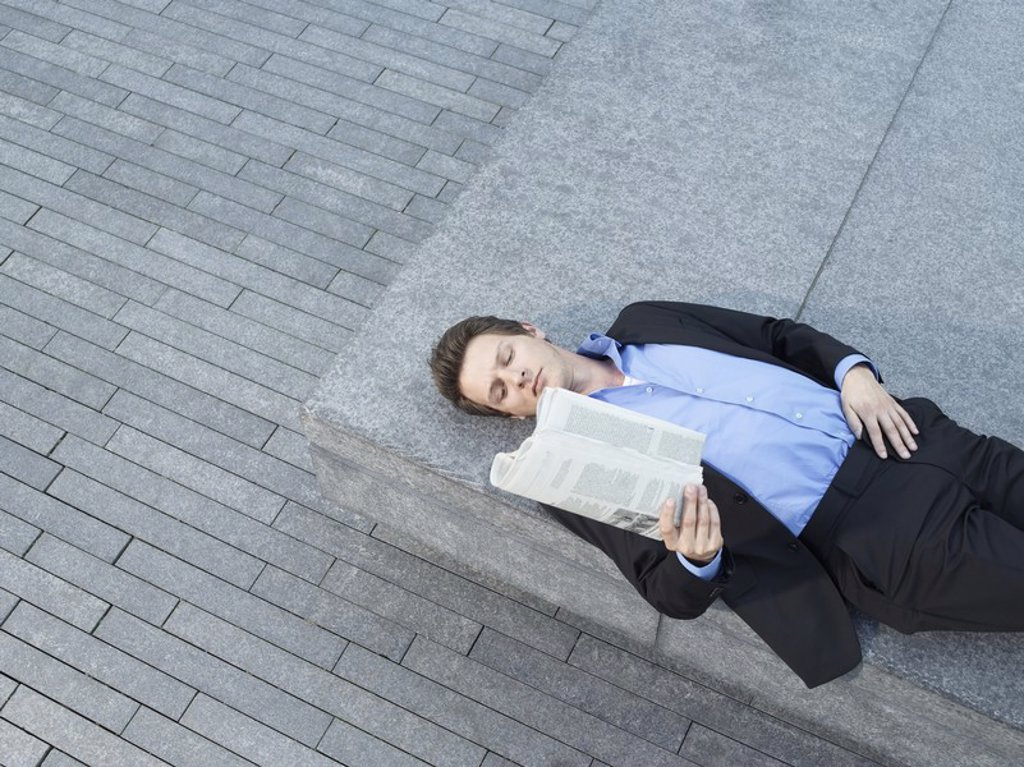Young businessman lying on wall on pavement reading newspaper elevated view : Stock Photo