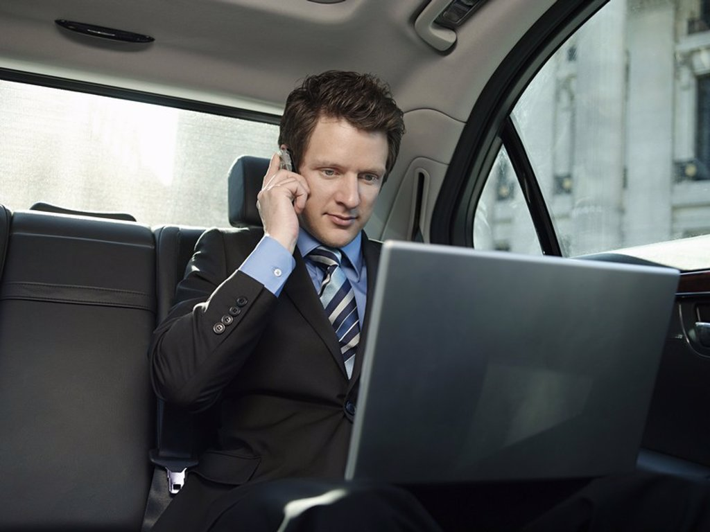 Stock Photo: 1654R-18034 Mid adult businessman sitting at back seat of car using laptop and mobile phone