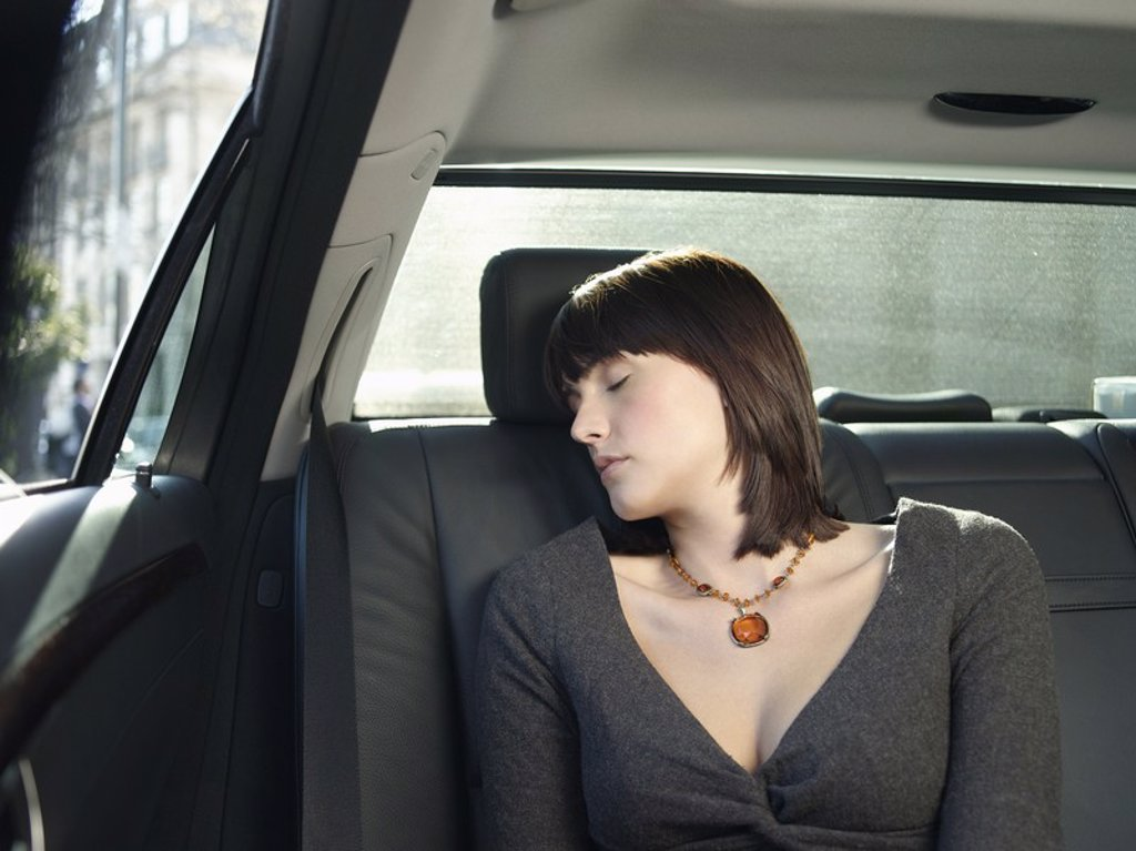Mid adult woman sleeping at back seat of car : Stock Photo