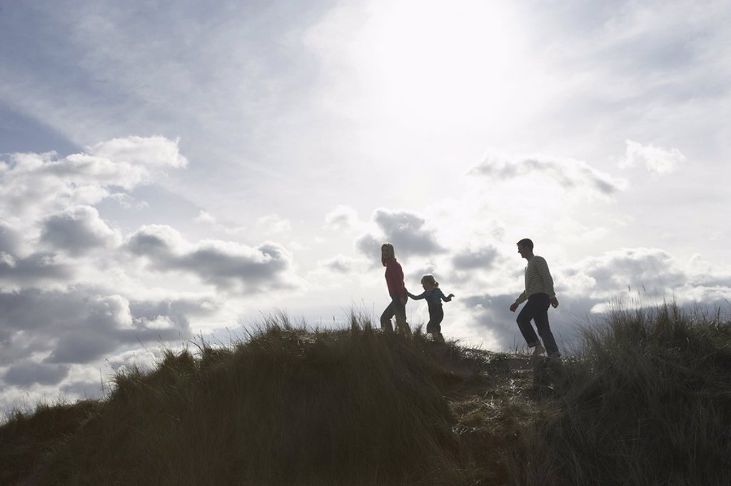 Silhouette of parents and daughter 5_6 walking on sand dunes : Stock Photo