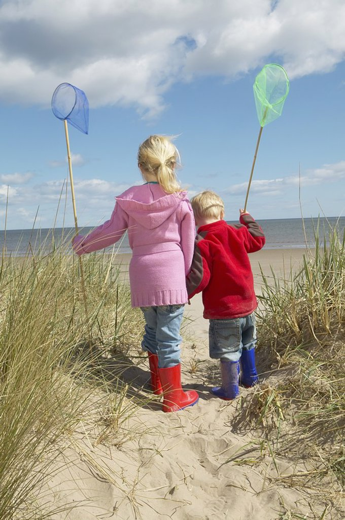 Brother and sister 4_6 with fishing nets standing on sand dunes : Stock Photo