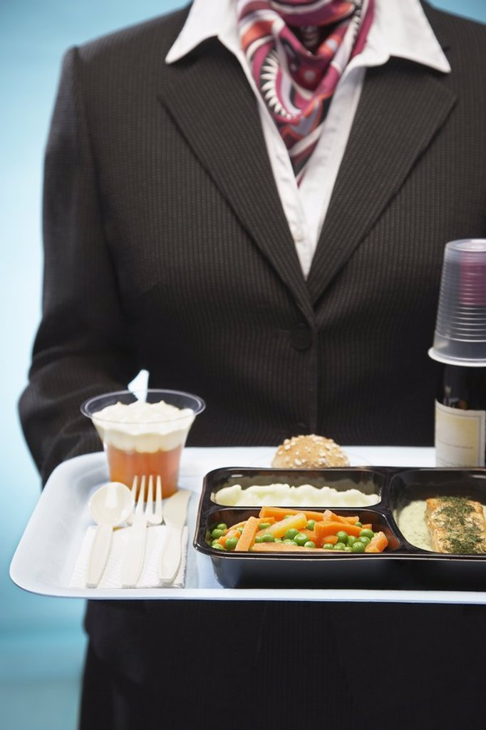 Stewardess holding tray with airplane food mid section : Stock Photo