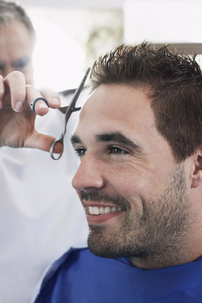 Barber cutting mans hair in barber shop close_up : Stock Photo