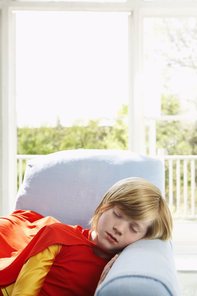 Young boy 7_9 sleeping in armchair wearing superhero costume indoors : Stock Photo