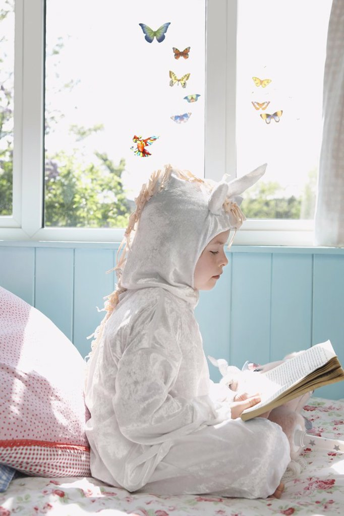 Young girl 5_6 sitting on bed in unicorn costume reading book side view : Stock Photo