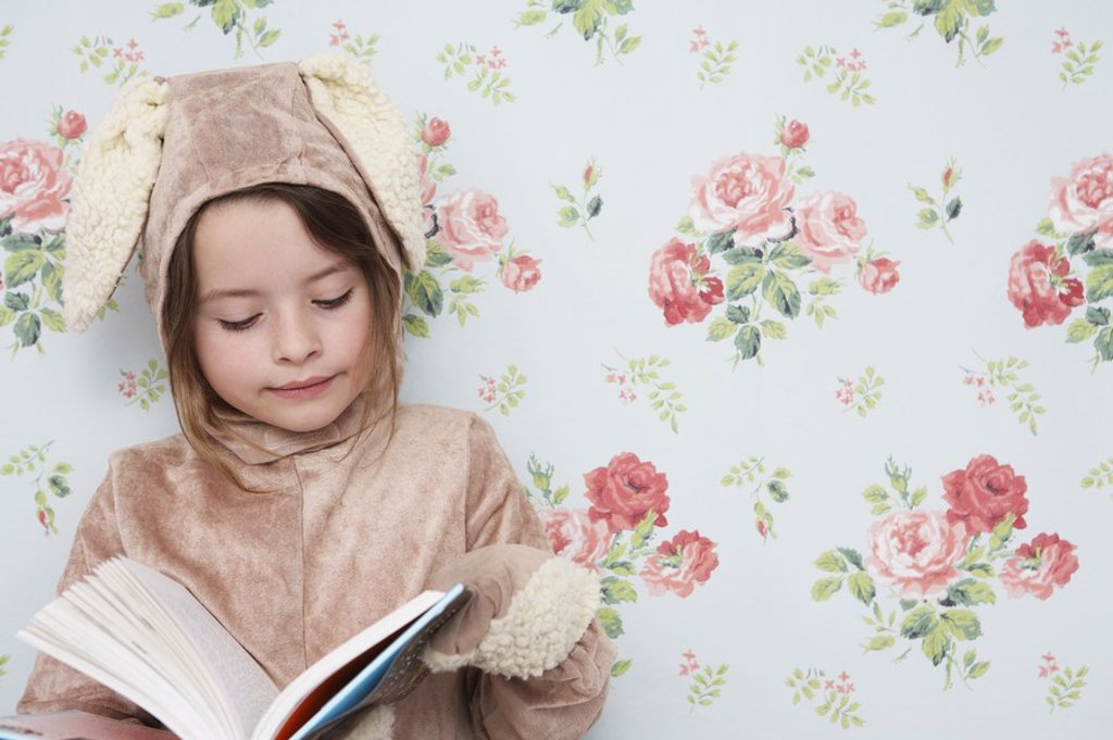 Stock Photo: 1654R-18652 Young girl 5_6 n bunny costume reading book wallpaper with floral pattern in background