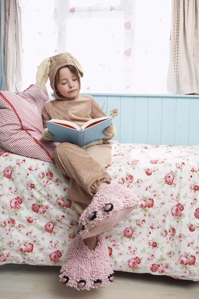 Stock Photo: 1654R-18655 Young girl 5_6 sitting on bed wearing bunny costume and monster slippers reading book