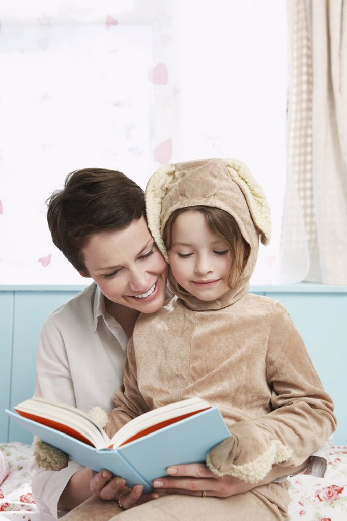 Mother and daughter 5_6 in bedroom reading book girl in bunny costume : Stock Photo