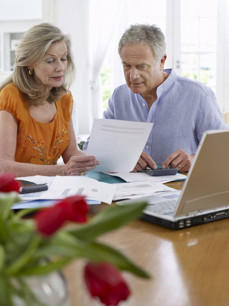 Senior couple looking at bills sitting at dining table : Stock Photo