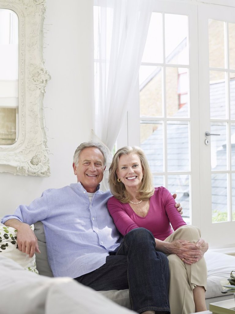 Senior couple sitting on sofa portrait : Stock Photo