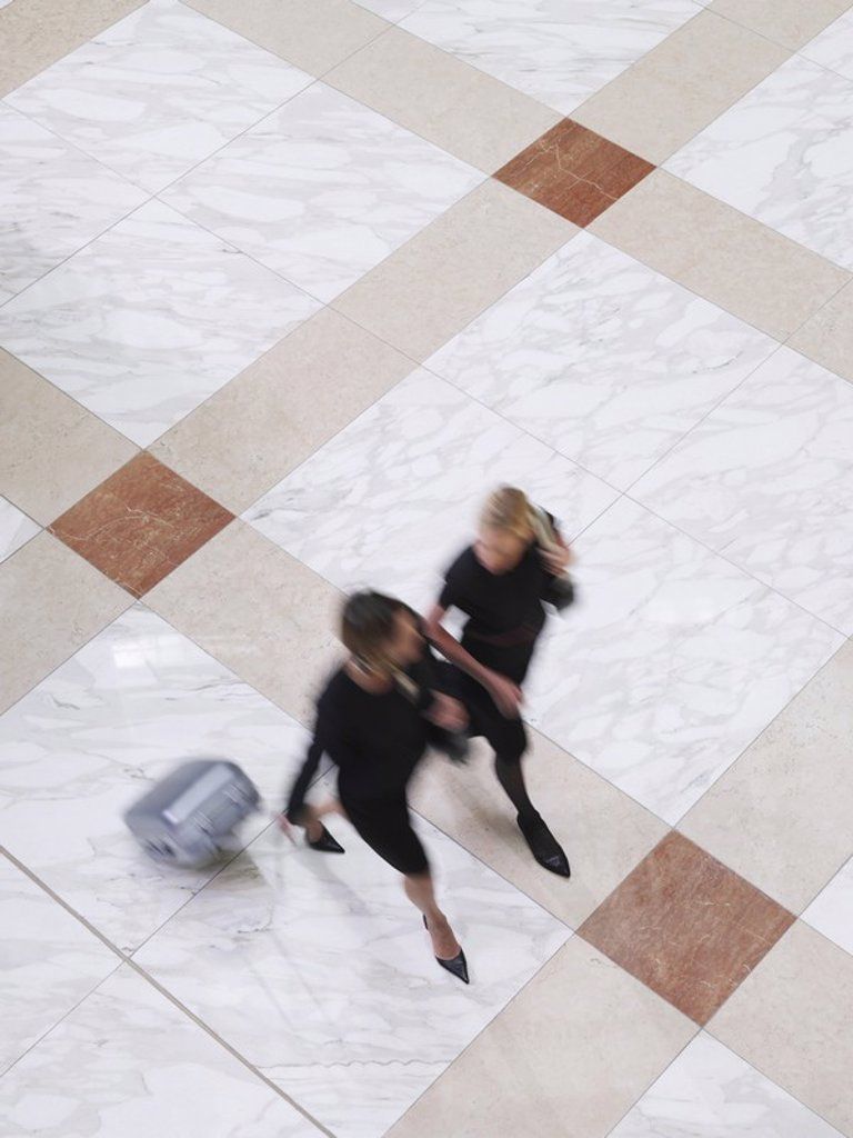 Two business women walking with suitcase elevated view long exposure : Stock Photo