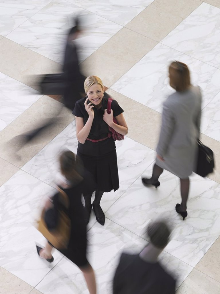 Stock Photo: 1654R-18770 Business woman using mobile phone standing amongst people walking elevated view long exposure