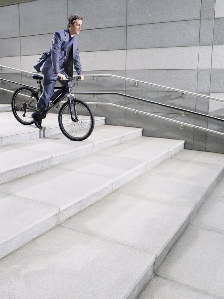 Stock Photo: 1654R-18793 Business man riding bicycle down steps side view
