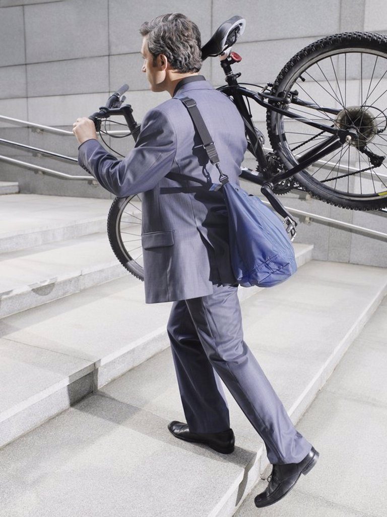 Business man carrying bicycle up steps side view : Stock Photo