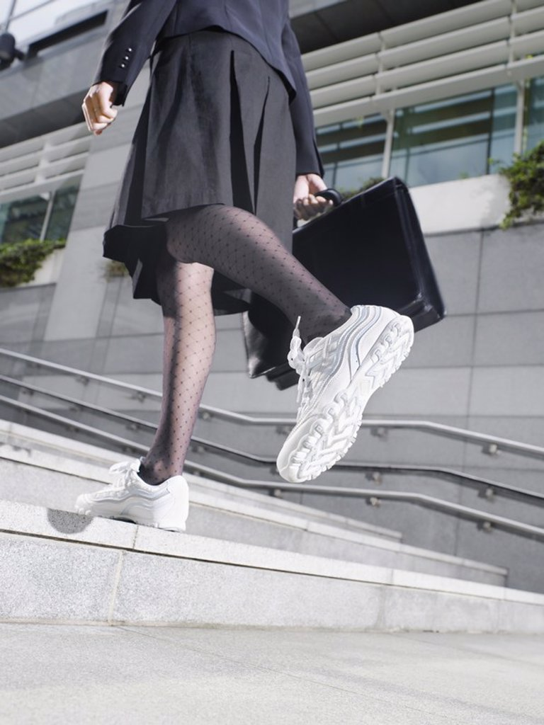 Business woman wearing running shoes walking up steps low section low angle view : Stock Photo