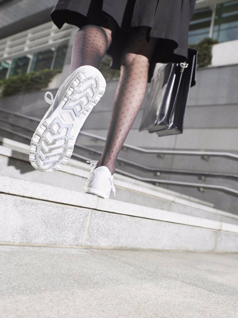 Stock Photo: 1654R-18799 Business woman wearing running shoes walking up steps low section low angle view back view