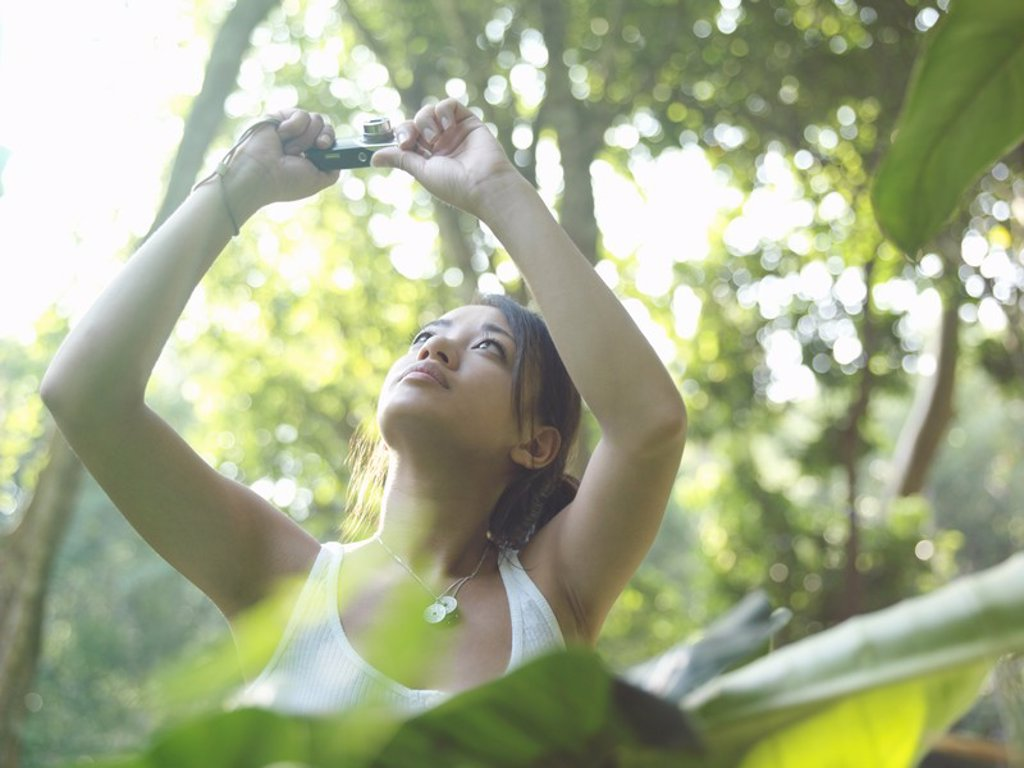 Young woman in forest taking photograph arms raised : Stock Photo
