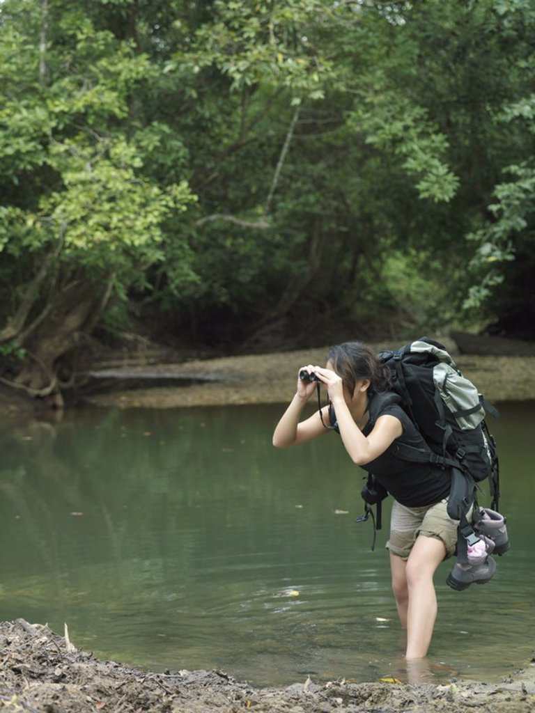 Young woman standing in water carrying backpack looking through binoculars : Stock Photo