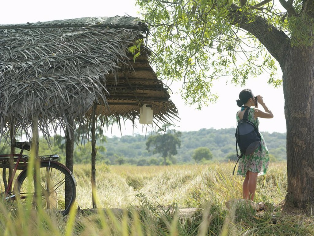 Young woman looking through binoculars bicycle under thatched roof : Stock Photo