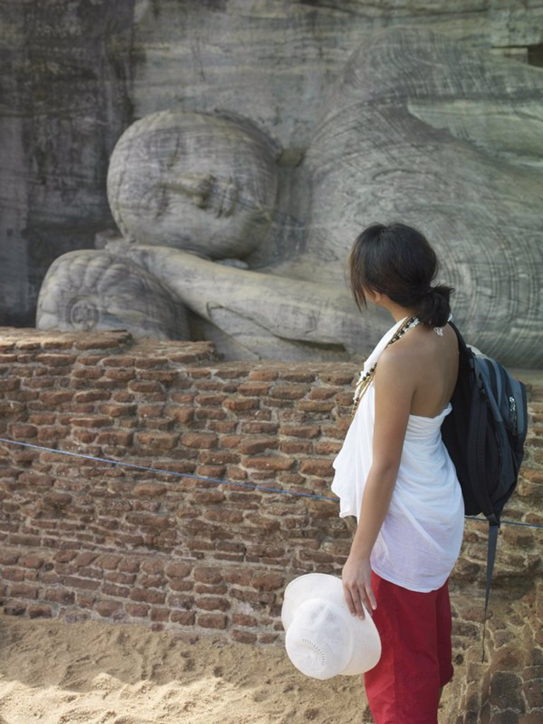 Young woman looking at statue of sleeping Buddha side view : Stock Photo