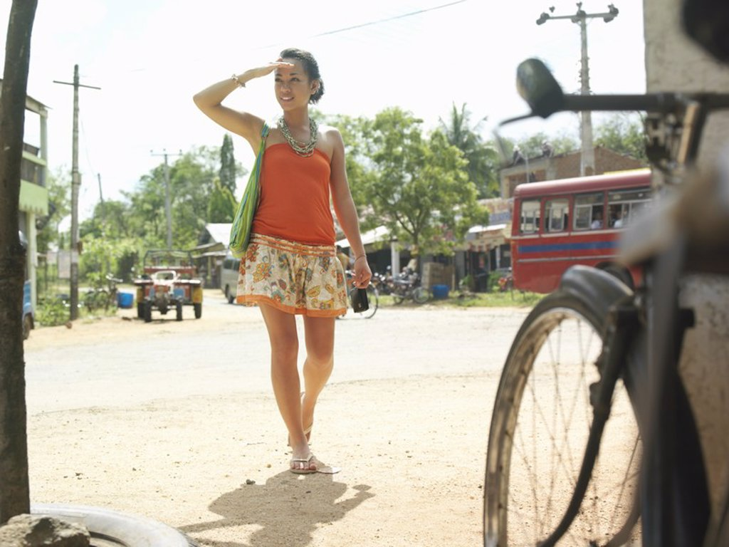 Young woman walking dirt road smiling : Stock Photo