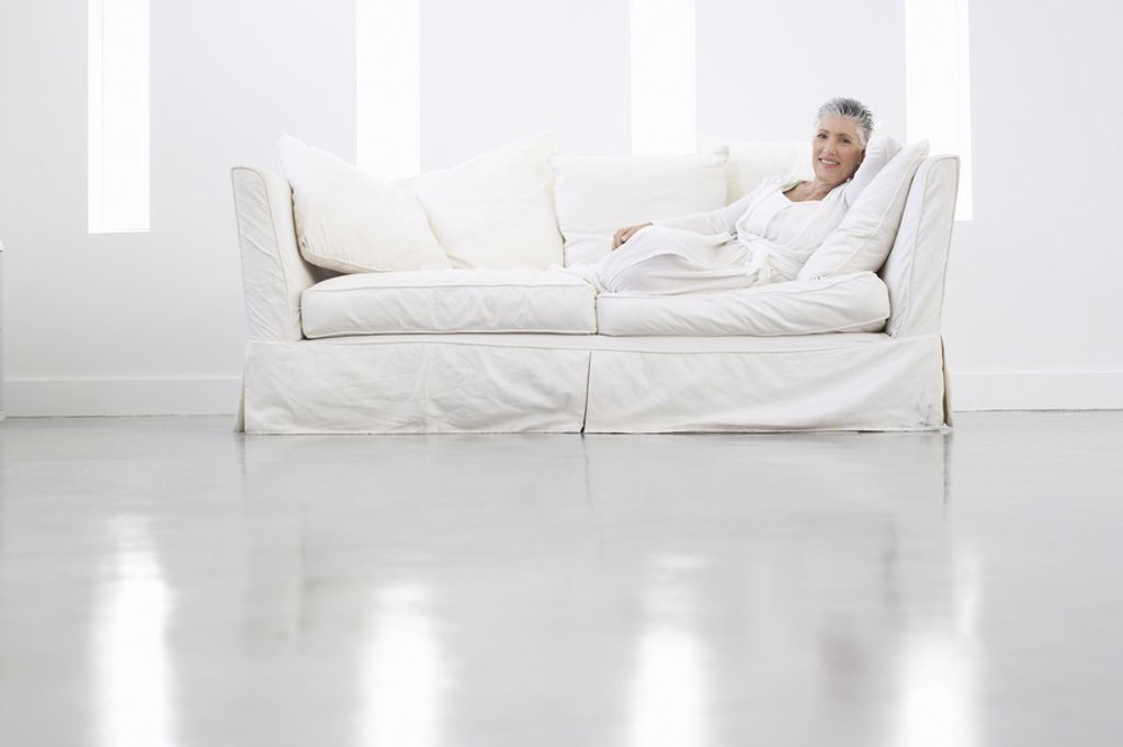 Stock Photo: 1654R-18908 Woman Relaxing on White Sofa