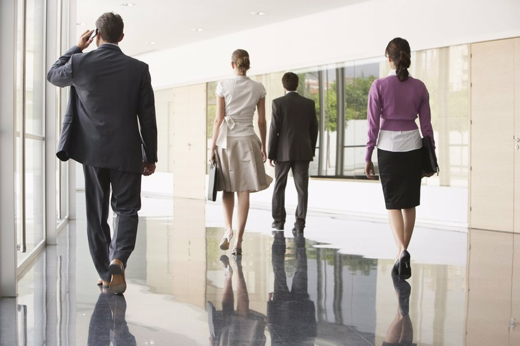Stock Photo: 1654R-18948 Four Businesspeople Walking in Office Corridor