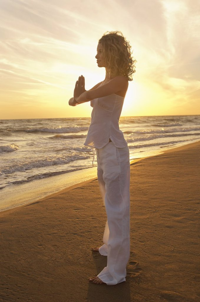 Young woman doing Tai Chi on beach side view : Stock Photo