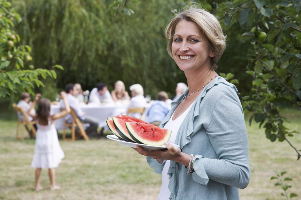 Woman with watermelon slices in garden family members in background : Stock Photo