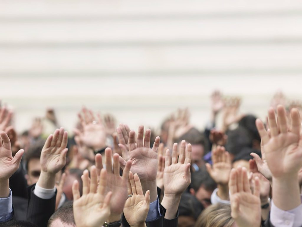 Crowd of people raising hands focus on hands : Stock Photo