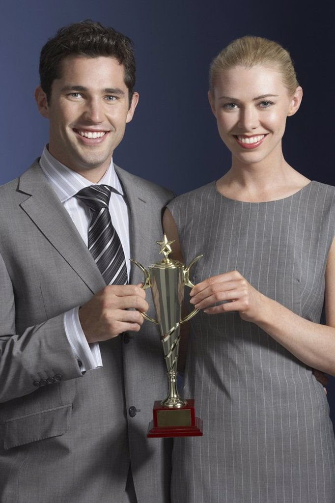 Stock Photo: 1654R-19140 Two business people holding trophy against dark background
