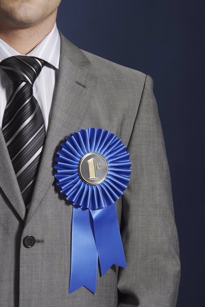 Stock Photo: 1654R-19142 Man wearing blue ribbon on lapel against dark background mid section