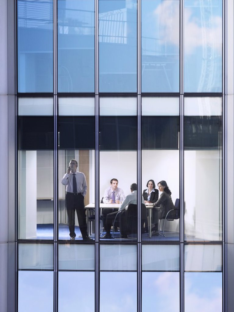Stock Photo: 1654R-19197 Group of business people at meeting in office view from building exterior
