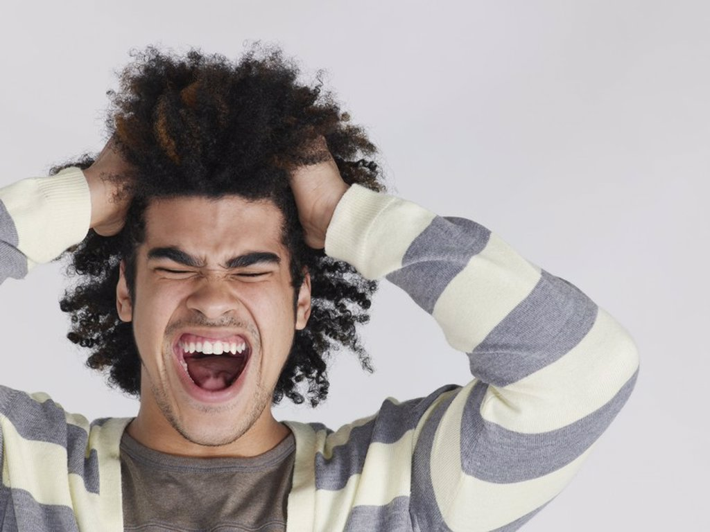 Young man with head in hands screaming : Stock Photo