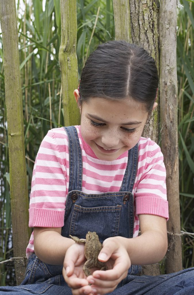 Girl 5_6 holding toad by fence : Stock Photo