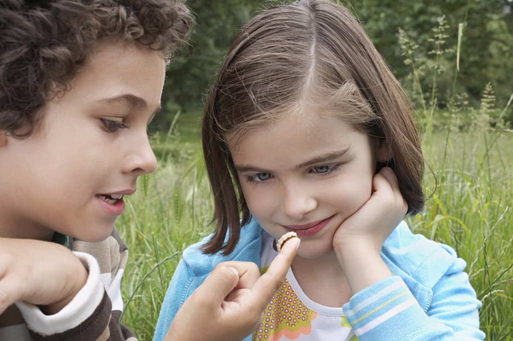 Brother and sister 7_9 examining caterpillar in field : Stock Photo