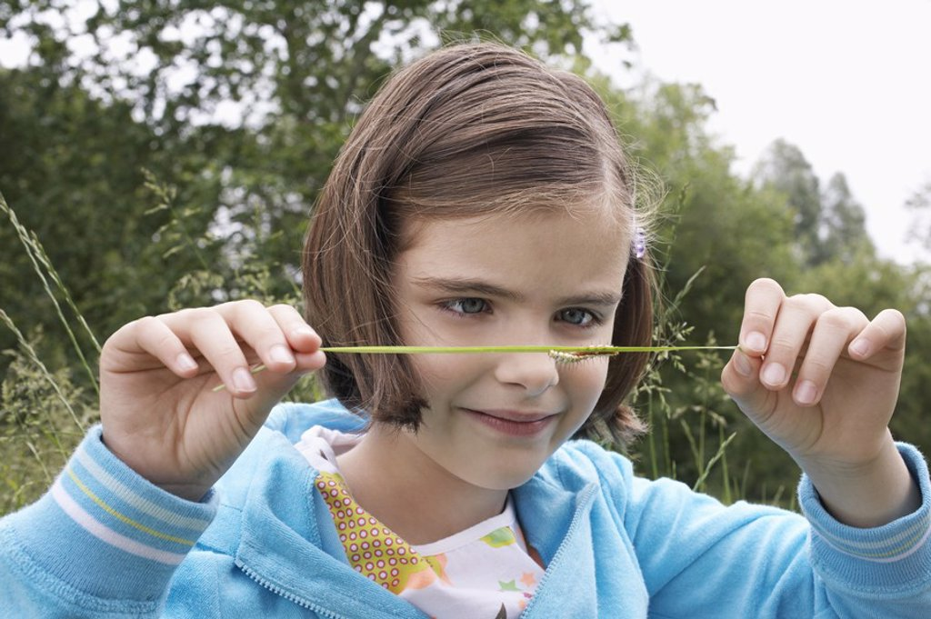 Stock Photo: 1654R-19531 Girl 7_9 examining caterpillar on grass in field