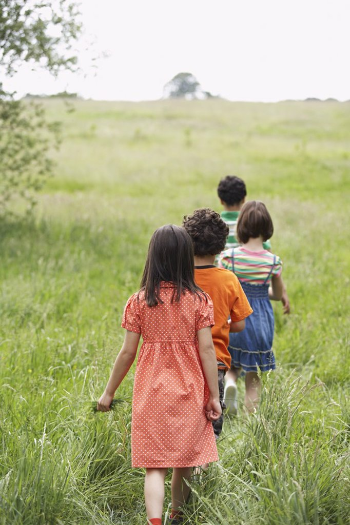 Children 7_9 walking in field : Stock Photo